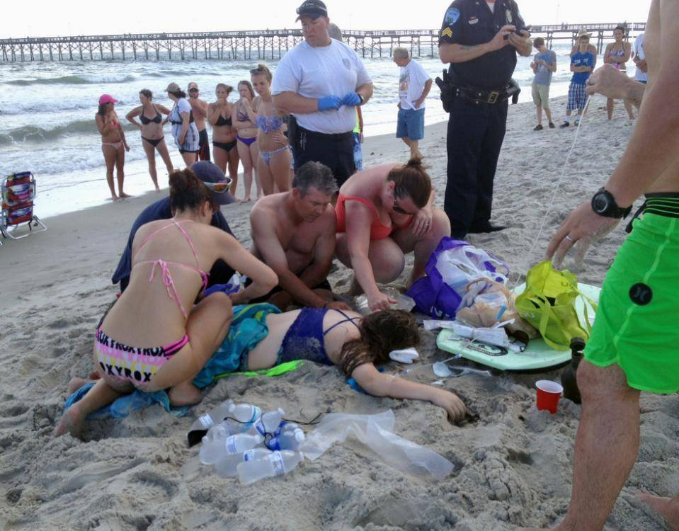 Emergency responders assist a teenage girl at the scene of a shark attack in Oak Island, N.C., Sunday, June 14, 2015. Mayor Betty Wallace of Oak Island, a seaside town bordered to the south by the Atlantic Ocean, said that hours after the teenage girl suffered severe injuries in a shark attack Sunday a teenage boy was also severely injured. (Steve Bouser/The Pilot, Southern Pines, N.C. via AP) MANDATORY CREDIT